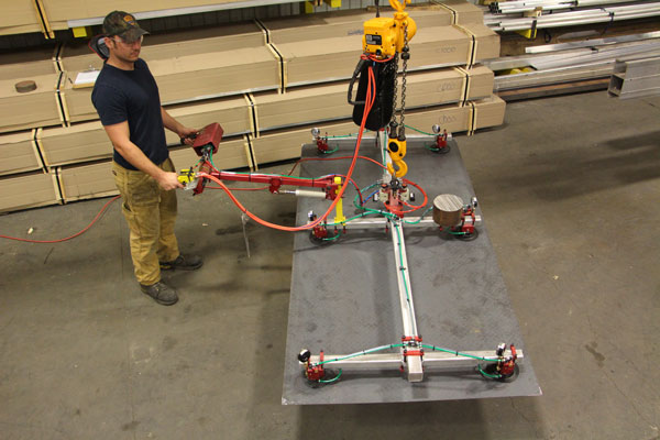 A vacuum end effector lifts a sheet of steel. This end effector can be hung from a G-Rail bridge crane.