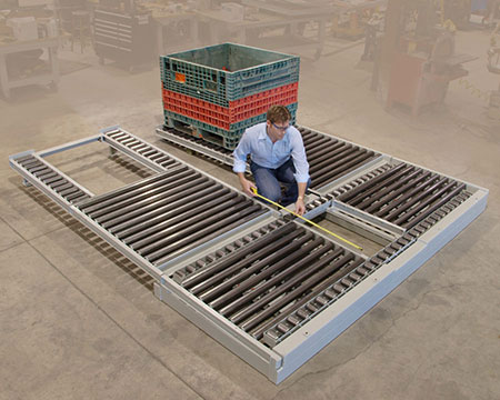 Gravity conveyor for plastic bins with pneumatic pop-up rollers for cross-transfer