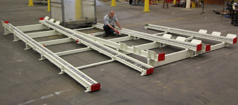 Gravity conveyor strands for auto parts pins, loaded and unloaded by forklift.
